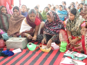 "The women brought their home piggybanks where to put ""extra"" rupees to bring to the savings meeting."