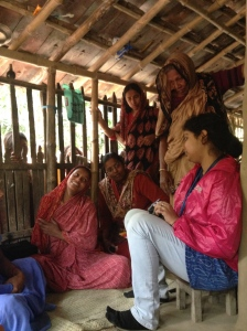 Sitting on the veranda talking with the community health worker, client and some of her family.