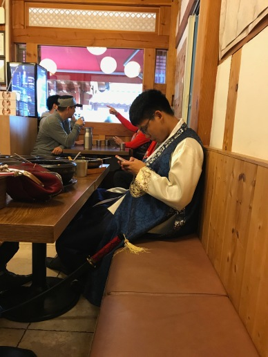 Teenage boy in hanbok on his cellphone